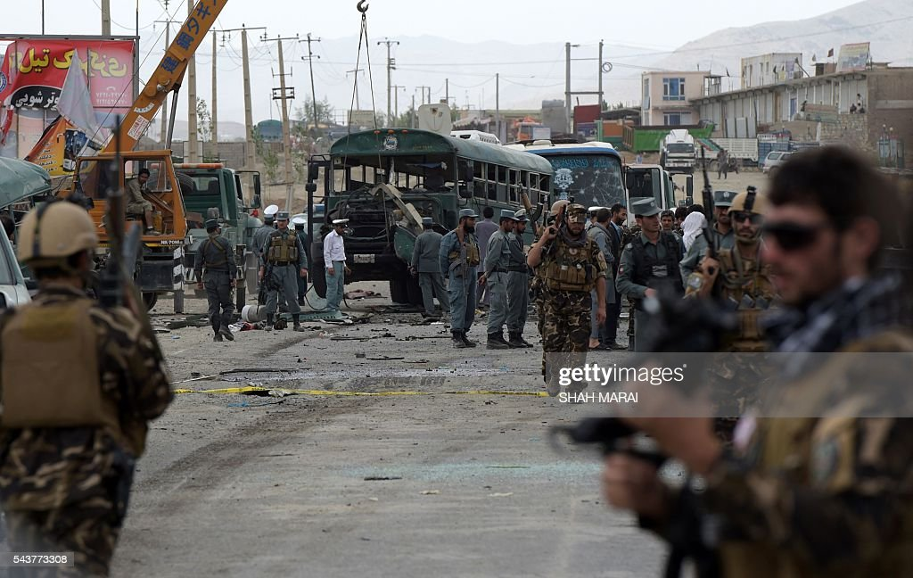 Afghan security personnel gather near the wreckage of buses which were carrying police cadets, at the site of a bomb attack on the outskirts of Kabul on June 30, 2016. At least 27 policemen were killed and 40 wounded after a bomb attack claimed by the Taliban struck a convoy of buses transporting police cadets in Kabul, the interior ministry said. / AFP / SHAH