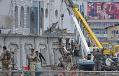 Afghan security personnel inspect the site of a car bomb attack at the gate of a government office in the Puli Mahmood Khan neighbourhood of Kabul on...