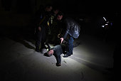 Afghan security personnel prepare to move a wounded man at the site of an attack on the Spanish embassy compound in Kabul on December 11 2015...