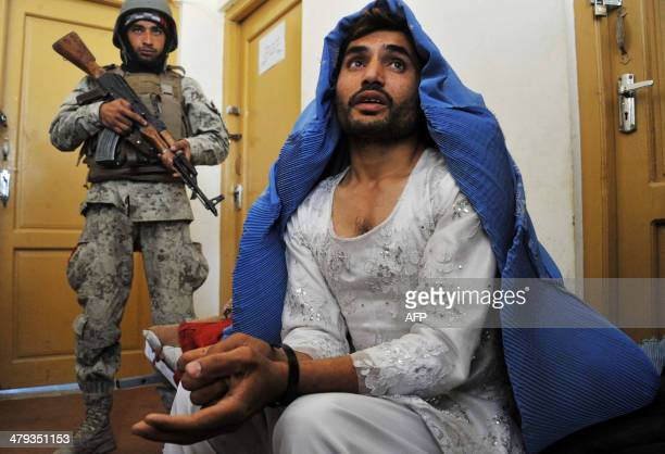 Afghan security personnel present a burqaclad resident they say is a Taliban fighter to the media at the Afghan National Army headquarters in...