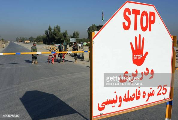 Afghan security personnel stand at a checkpoint outside Jalalabad Airport where a US C130 military transport plane crashed in Jalalabad on October 2...
