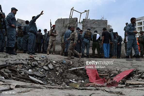Afghan security personnel stand at the scene of a suicide attack by Taliban militants on the Afghan parliament building in Kabul on June 22...