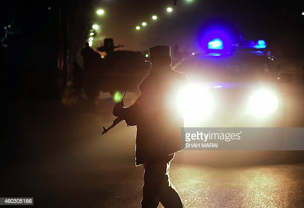 Afghan security personnel stand guard near the site where a bomber blew himself up in the audience watching a theatre show at the Istiqlal High...