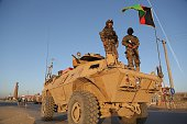 Afghan security personnel stand guard on an armoured vehicle at a checkpoint in Ghazni on October 13 2015 Fighting flared in eastern Afghanistan on...