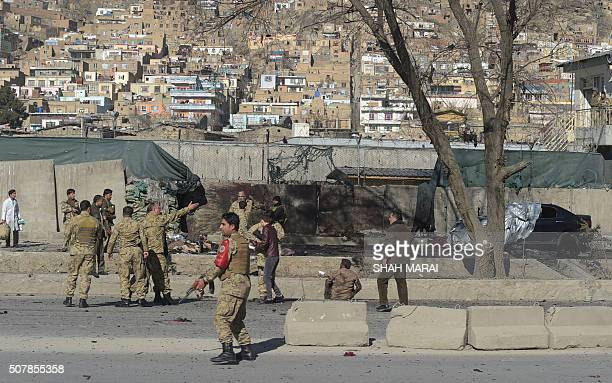 TOPSHOT Afghan security personnels gather as victims are treated at the site of a suicide car bomb next to a police base in Kabul on February 1 2016...