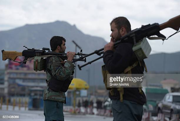 Afghan security personnels keep watch at the site of car bomb attack in the Puli Mahmood Khan neighbourhood of Kabul on April 19 2016 A powerful...