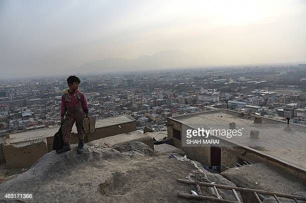 Afghan shoeshine boy Sameiullah looks on from a hillside towards the KartaeSakhi cemetery where he waits for customers daily in Kabul on February 10...