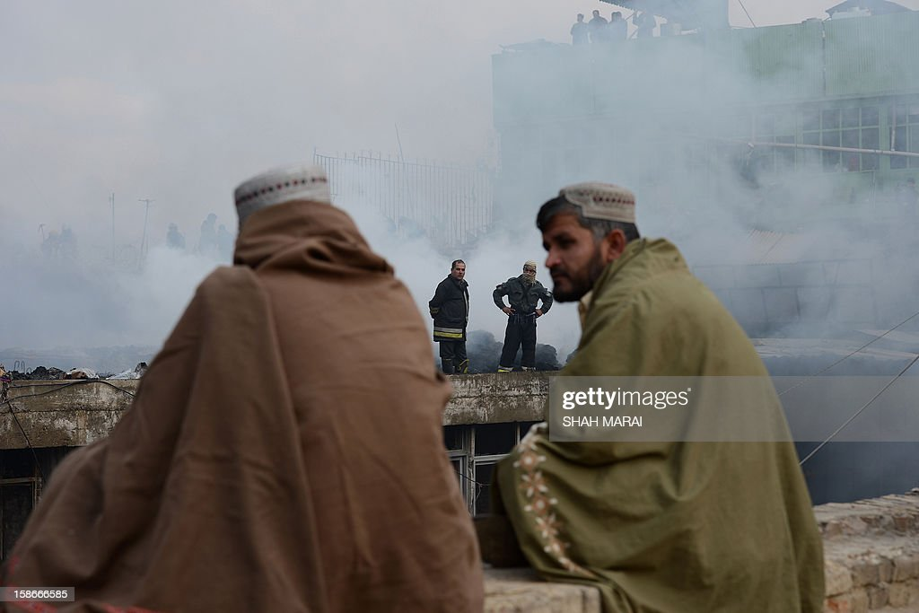 Afghan shopkeepers (foreground) look on as firefighters work over the remains of shops after a huge fire swept through a market in Kabul on December 23, 2012. A huge fire swept through a market in downtown Kabul on December 23, destroying hundreds of shops and forcing the city's nearby money exchange to evacuate, police and witnesses said. There were no reports of any casualties in the early morning blaze which destroyed most of the cloth market's 500 shops, Kabul fire department officials told AFP. AFP PHOTO/ SHAH Marai