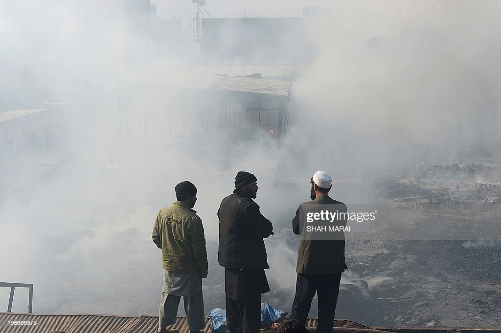 Afghan shopkeepers look on as they stand over the smoldering remains of shops after a huge fire swept through a market in Kabul on December 23, 2012. A huge fire swept through a market in downtown Kabul on December 23, destroying hundreds of shops and forcing the city's nearby money exchange to evacuate, police and witnesses said. There were no reports of any casualties in the early morning blaze which destroyed most of the cloth market's 500 shops, Kabul fire department officials told AFP. AFP PHOTO/ SHAH Marai