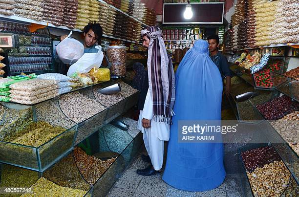 Afghan shoppers buy dried fruits ahead of the Eidal Fitr festival which marks the end of Ramadan at a market in Herat on July 13 2015 Afghan Muslims...
