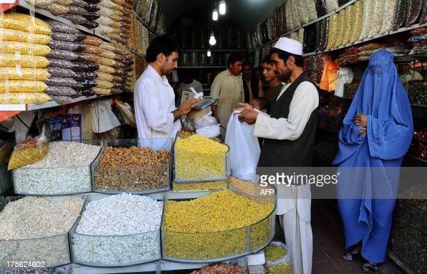 Afghan shoppers buy dry fruits and sweets for the Eid festival which marks the end of the Muslim holy month of Ramadan at a market in Herat on August...