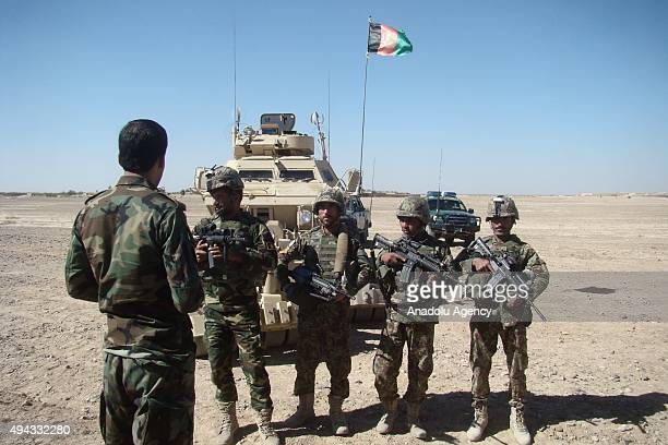 Afghan soldiers inspect an area after the Afghan security forces clashed with the Taliban militants in the Helmand Province Afghanistan on October 26...