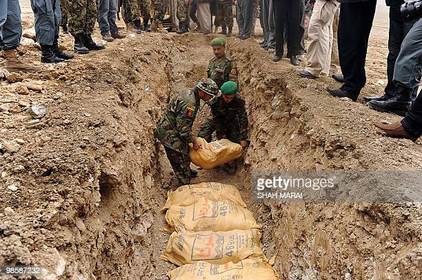 Afghan soldiers place bags of ammonium nitrate fertilizer into a freshly dug trench on a hillside north of Kabul on April 21 before their destruction...