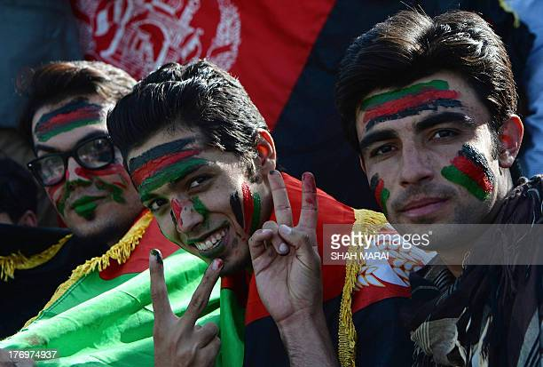 Afghan spectators their faces painted with the colours of their national flag pose as they watch their team play against Pakistan at the Afghanistan...