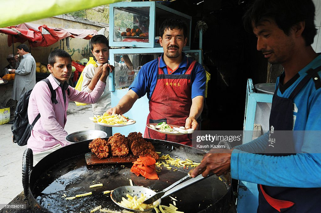 Afghan style hamburger and chips are cooked and served from a big pan placed outside a shop on October 20, 2011 in Kabul, Afghanistan.