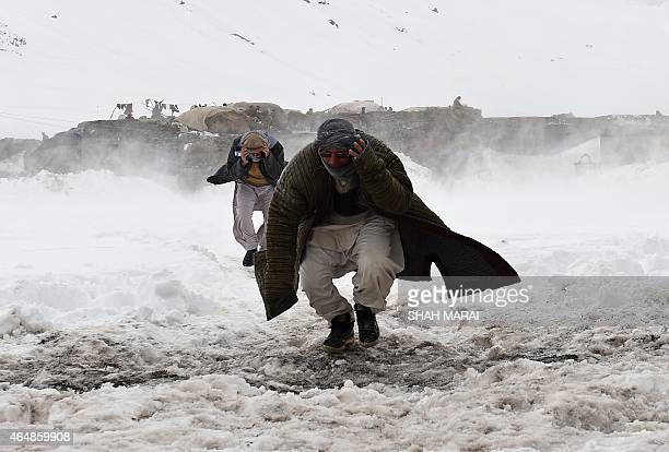 Afghan survivors of an avalanche run to get relief goods distributed by an Afghan army helicopter in the Paryan district of Panjshir province north...