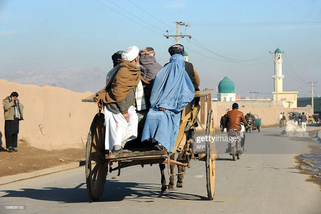 Afghan travellers journey on a horse cart along a street in Herat on December 30, 2012. Over a third of Afghans are living in abject poverty, as those in power are more concerned about addressing their vested interests rather than the basic needs of the population, a UN report said. AFP PHOTO/ Aref Karimi