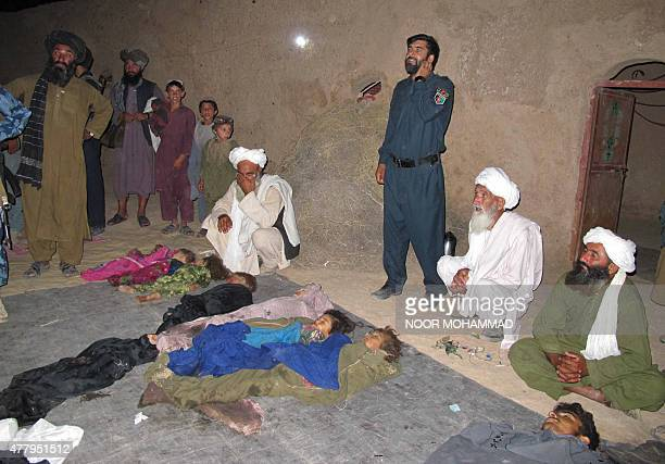 Afghan villagers gather around the bodies of children who were killed by a roadside bomb in Helmand late on June 20 2015 A roadside bomb killed at...