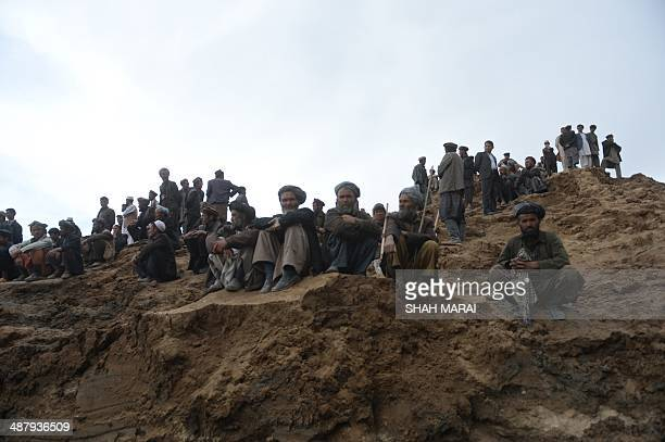 Afghan villagers gather at the site of a landslide in the Argo district of Badakhshan province on May 3 2014 Rescuers searched in vain for survivors...