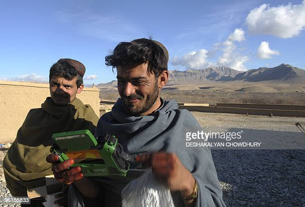 Afghan villagers listen to a radio given as a gift from Dutch soldiers of Charlie Air assault company at Forward Operational Base of Mirwais in the...