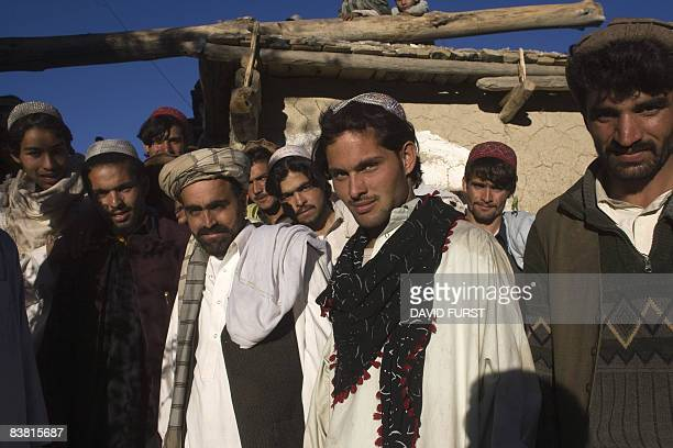 Afghan villagers stand for a family photo during a traditional Afghan wedding party of a fellow villager Nazirdjan as US Army soldiers from 2506...