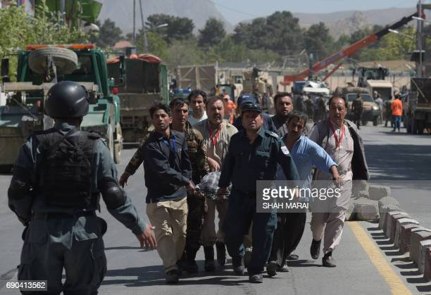 Afghan volunteers carry victims at the site of a car bomb attack in Kabul on May 31 2017 At least 80 people were killed and hundreds wounded May 31...
