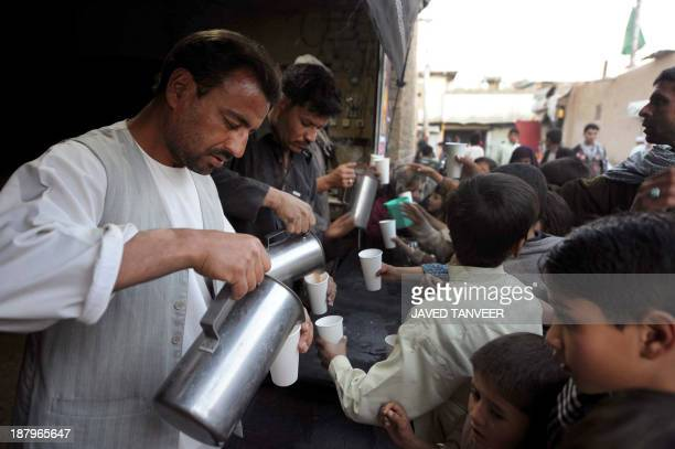 Afghan volunteers pour milk and tea for the people as Shiite Muslims participate in a ritual to commemorate the martyrdom of Imam Hussain the...