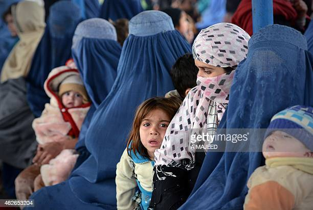 Afghan women and their children sit at The United Nations High Commissioner for Refugees repatriation center on the outskirts of Peshawar on February...