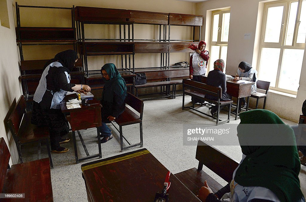 Afghan women are assisted by election officials as they give details to obtain their voter registration cards at an election registration centre in Kabul on May 26, 2013. Afghanistan began registering voters on May 26, for elections to be held next year when NATO forces withdraw and leave the mammoth task of security to a tottering government amid growing insurgency. Registration began in 41 centres in all 34 provinces for those who have turned 18, previously not registered and those who have lost their old voter registration cards. AFP PHOTO/ SHAH Marai