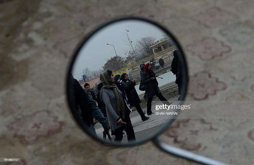 Afghan women are pictured in the mirror of a motorcycle as they march during a protest calling for an end to violence against women in Afghanistan and around the world, in Kabul on February 14, 2013. According to a UN report, Afghanistan has made progress in protecting women against violence, but many still suffer horrific abuse 11 years after a US-led invasion brought down the Taliban regime. Afghan women still endure killings by relatives in the name of family honour, forced marriages and domestic abuses. AFP PHOTO/SHAH Marai