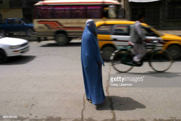 Afghan women crosses the street on April 10 2004 in Kabul Afghanistan Women in Afghanistan mostly covered once they are outside their homes The...