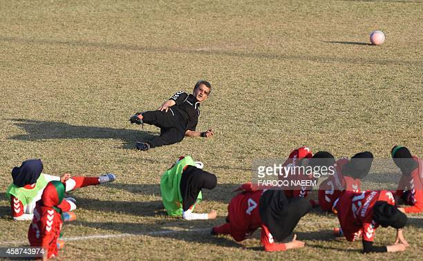 Afghan women football team coach Faqir Zada exercises with team players during a practice ahead of the South Asia Football Federation women's...