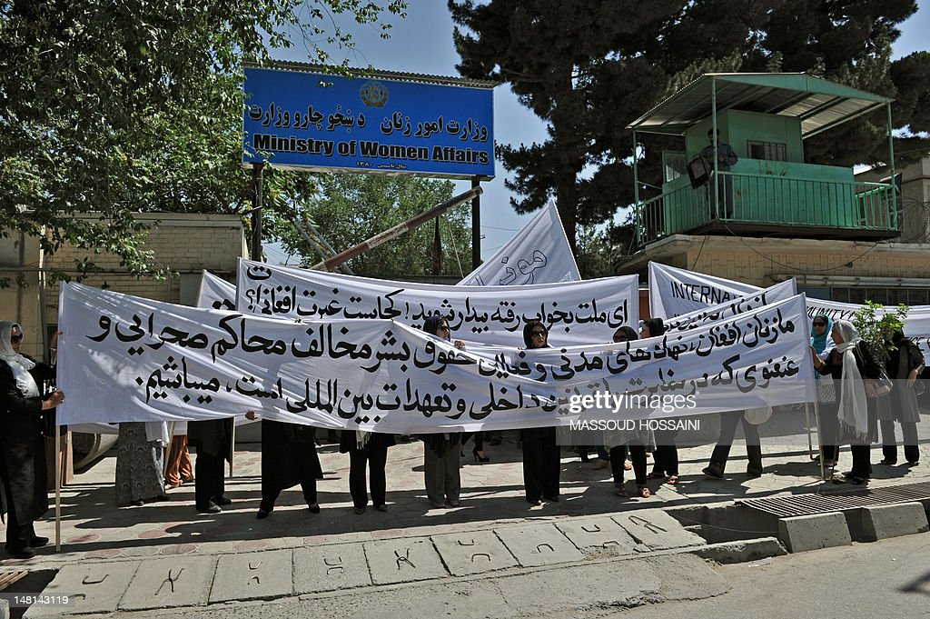 Afghan women hold up banners in front of the Ministry of Women's Affairs to protest the recent public execution of a young woman for alleged adultery, in Kabul on July 11, 2012. Dozens of Afghan women's rights activists took to the streets July 11 to protest the recent public execution of a young woman for alleged adultery, which was captured in ahorrific video. AFP PHOTO/Massoud HOSSAINI