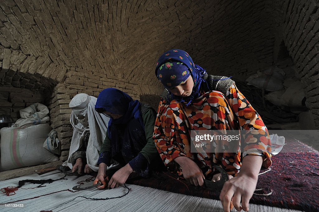 Afghan women of Turkmen ethnicity weave a rug in the Balkh province village of Siah Gerd on March 10 2012 Mazari Sharif which means respected shrine...