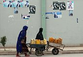 Afghan women push wheelbarrows filled with jerry cans walk past electoral posters of election candidates along a street in Kandahar on April 1 2014...