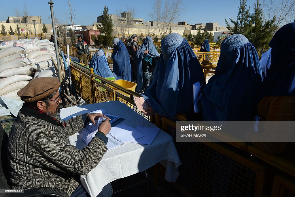 Afghan women register their names to receive winter supplies at a UNHCR distribution centre for needy refugees at the Women's Garden in Kabul on January 2, 2013. Hundreds of families living in makeshift shelters around the Afghan capital Kabul collected blankets, charcoal and other supplies on January 2 as authorities struggle to avoid last year's deadly winter toll. With temperatures dropping to -10 Celsius (14 Fahrenheit) at night in the city, the 35,000 refugees who live in the snow-covered camps face a battle to survive dire conditions protected only by plastic sheeting. Despite Afghanistan receiving billions of dollars of aid since 2001, more than 100 children died last year during the harshest winter in two decades, and the UN refugee agency has co-ordinated efforts to avoid repeat fatalities. AFP PHOTO/ SHAH Marai