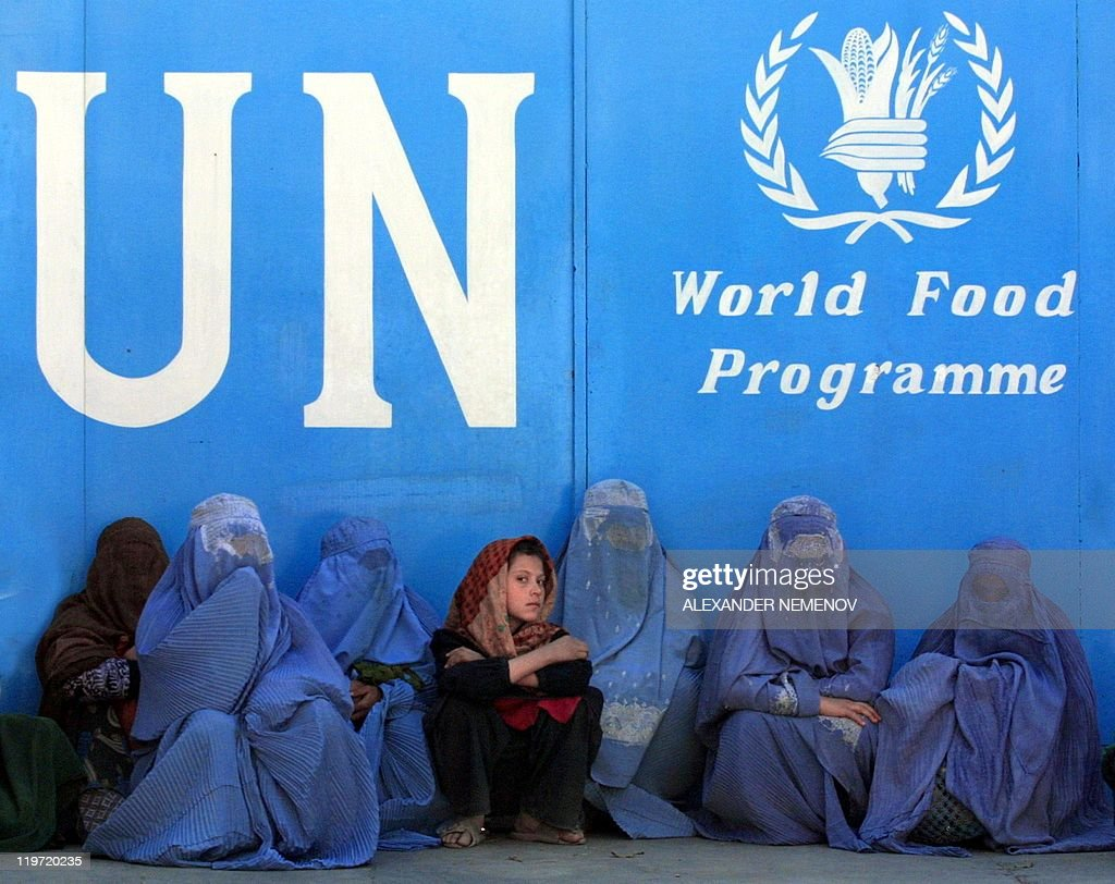 Afghan women sit in front of the UN World Food Programme headquarters in Kabul 24 November 2001 waiting for a chance to get some food give outs The...