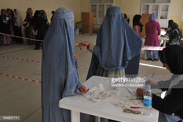 Afghan women talk as they register to cast their votes at a polling station in Kabul on September 18 2010 Afghanistan began voting for a new...