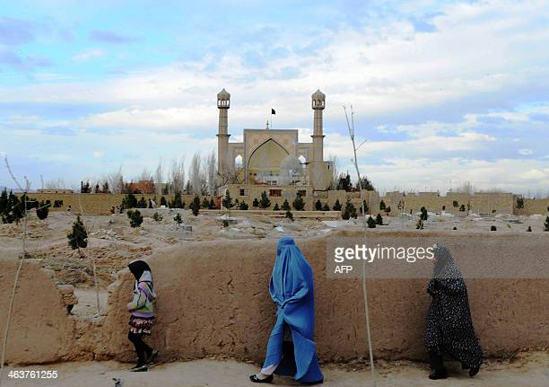 Afghan women walk outside a graveyard alongside a shrine in Herat on January 19 2014 Afghanistan remains an extremely poor country where one in three...
