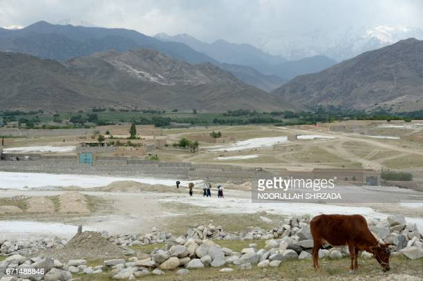 Afghan women walk through a village near the site of a bomb attack by US forces in the Achin district of Nangarhar province on April 22 2017 Afghan...