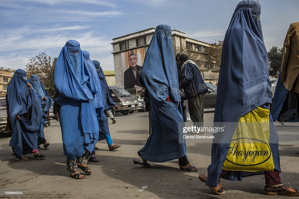 Afghan women walk through the street, as a poster of President Hamid Karzai is seen on the outside City Hall on November 7, 2012 in Kabul, Afghanistan.