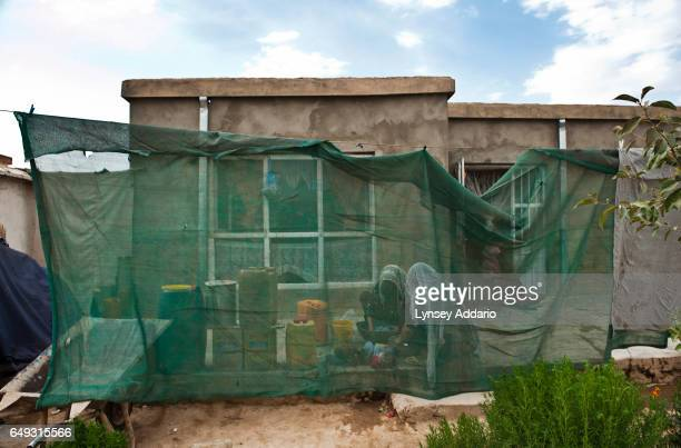Afghan women wash clothes behind a makeshift screen in the mostly abandoned land allocation settlement of AliceGhan about 30 miles outside of Kabul...