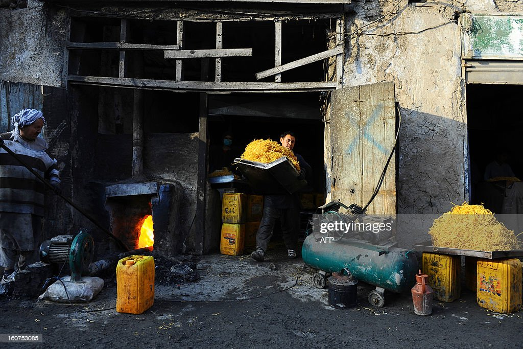 Afghan worker (L) stokes a fire as another prepares a local snack food called seemian, made from flour and sugar, at a factory in Mazar-i-Sharif on February 2, 2013. Afghanistan's economy will easily survive the pending departure of US and other international troops next year, Afghan Finance Minister Omar Zakhilwal insisted last month.