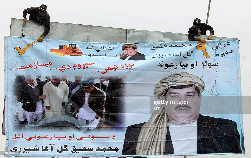 Afghan workers erect an election campaign poster of politician Gul Agha Shirzai in Kandahar on February 5 2014 Taliban insurgents have threatened to...