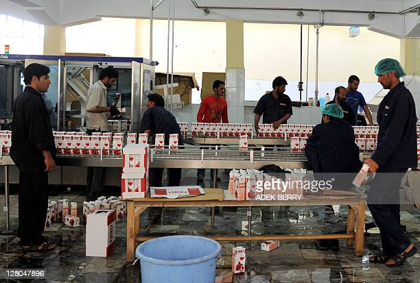 Afghan workers package fruit juice at a food processing factory in Kabul on October 3 2011 According to a recent report from the Afghanistan...
