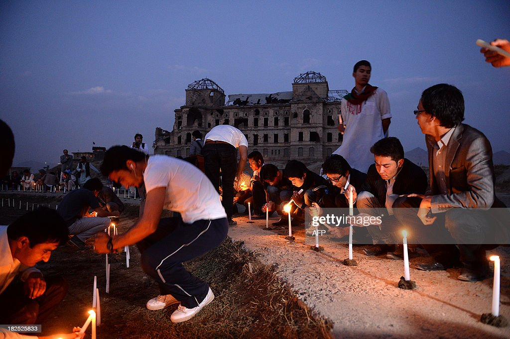 Afghan youth light candles in front of the destroyed palace of Darul Aman to mark the killing of 5000 civilians by the communist regime during the Russian occupation, in Kabul on September 29, 2013.Afghanistan began two days of official mourning for people killed by the communist regime in the late 1970s after a list of thousands of the dead was released. AFP PHOTO/ Massoud HOSSAINI