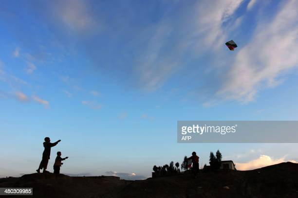 Afghan youths fly kites during sunset on the outskirts of Jalalabad Nangarhar province on March 24 2014 Some nine million Afghans or 36 percent of...