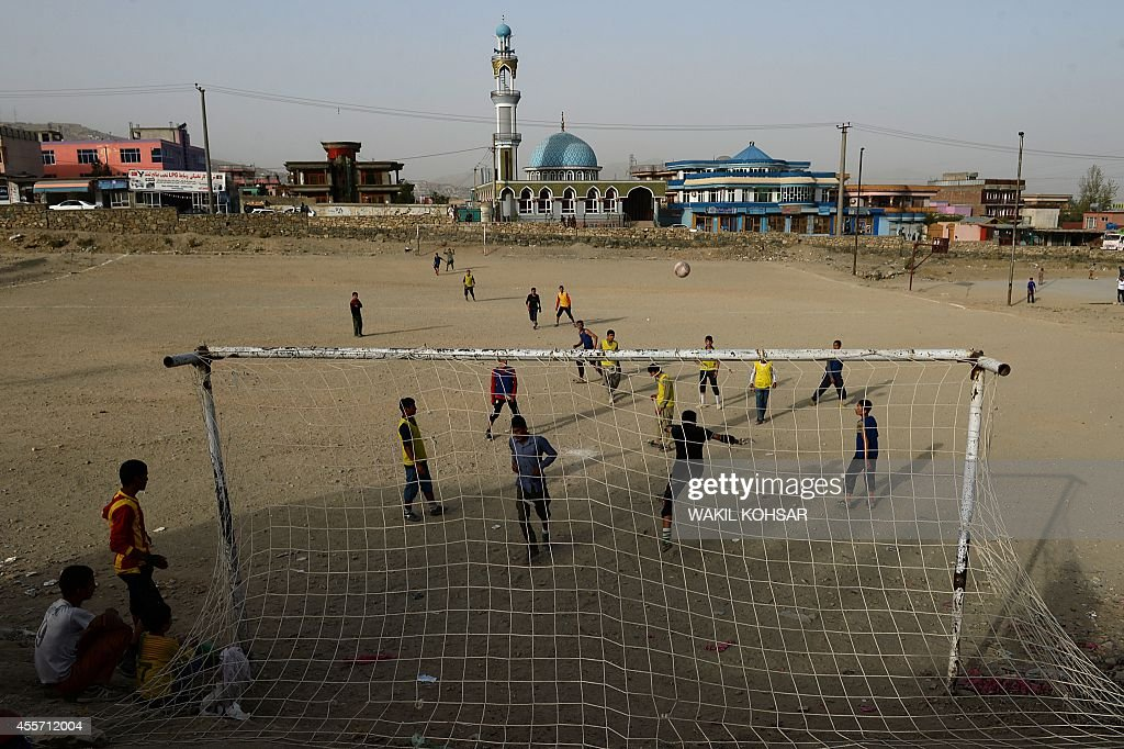 Afghan youths play football at a field in the outskirts of Kabul on September 19, 2014. Football is a popular sport in the war-torn country, with the Afghan national football team winning last years South Asian Football Championship. AFP PHOTO/Wakil Kohsar