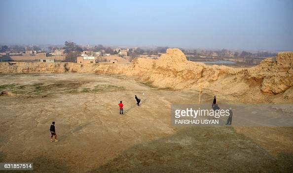 TOPSHOT Afghan youths play football on a field in MazariSharif on January 13 2017 / AFP / FARSHAD USYAN