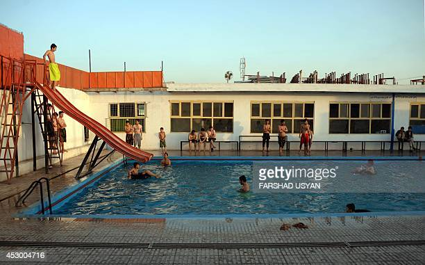 Afghan youths swim in a public swimming pool in MazariSharif on July 31 2014 Temperatures in the city are expected to peak around 36 degrees Celcius...